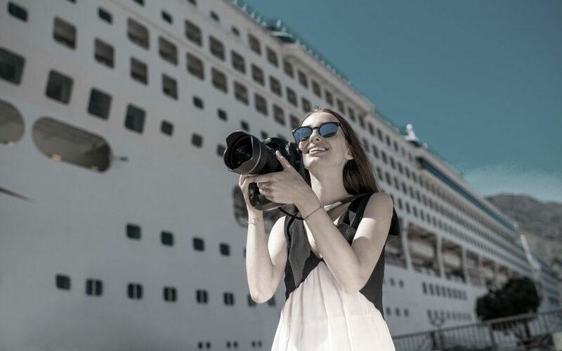 Frau mit Kamera vor Kreuzfahrtschiff