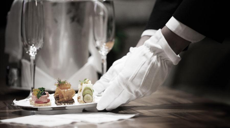Kellner bringt Speisen auf der Queen Mary 2 an den Tisch (Galley Tour)