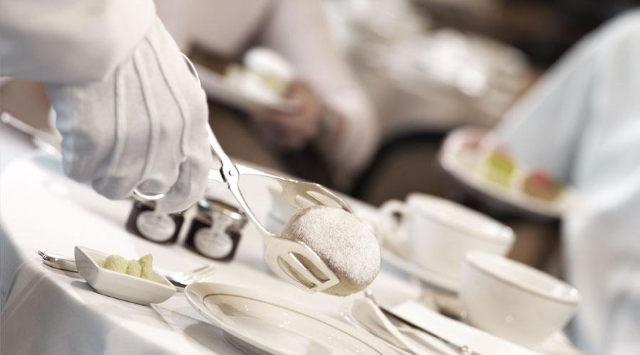 Kellner richtet Dessert auf der Queen Mary 2 an
